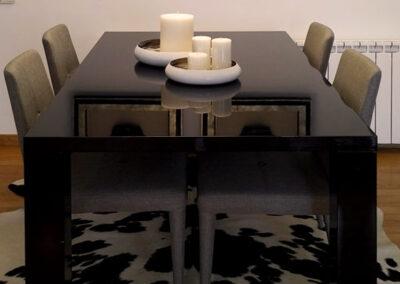 Comedor en blanco y negro con decoración étnica y alfombra de piel de vaca
