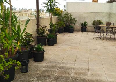 Terraza con jardín y mobiliario en hierro