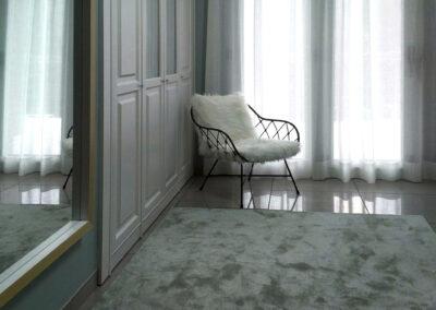 Dormitorio detalle zona armario sillón de mimbre y hierro con cojin en pelo blanco
