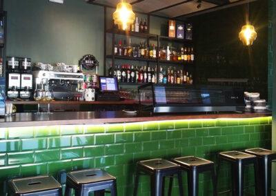 barra alicatada en verde inglés, retroiluminación y taburetes estilo industrial negros