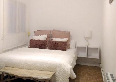 dormitorio en blanco, coordinado de cojines en rosa nude y pie de cama rustico en madera natural