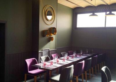 zona comedor sillas tapizadas en lino lilas y verdes decoración vertical en dorado