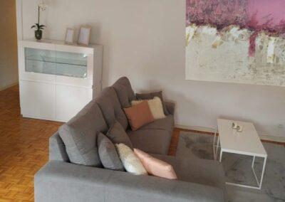 Mobiliario de salón mesita auxiliar y mueble aparador en blanco y cuadro arte abstracto tonos rosas