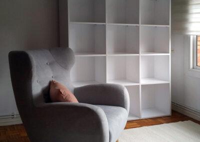 zona de lectura con librería en blanco, butaca en lino gris y cojín en rosa alfombra en gris