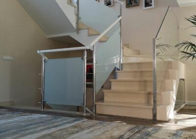 Recibidor abierto al salón con alfombra en tonos azules y beige  y collage de fotos en escalera