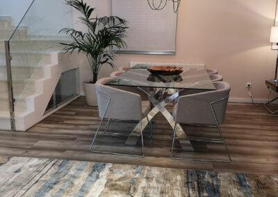 zona comedor, mesa cristal e inox, cuenco madera teka y lampara de techo pop Fest