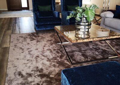 salón con tapiceria en terciopelo azul alfombra marrón chocolate mesa de centro en inox y madera rustica