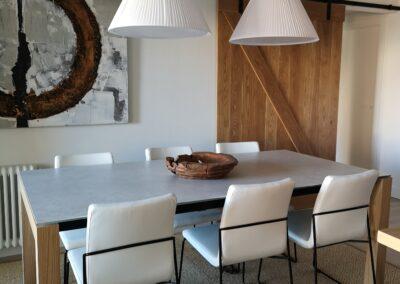Salón comedor con puerta corredera de madera de fondo.