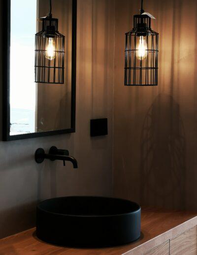 Detalle lavabo con griferia y lampara colgante en negro